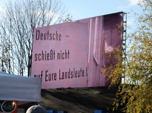 "One of many giant screens along the route that are playing video images from the Cold War. This one says, ""Germans, don't shoot your own countrymen."""
