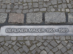 A plaque marking where the Wall ran along one of Berlin's streets.